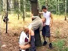 Three boys lick each other outdoors